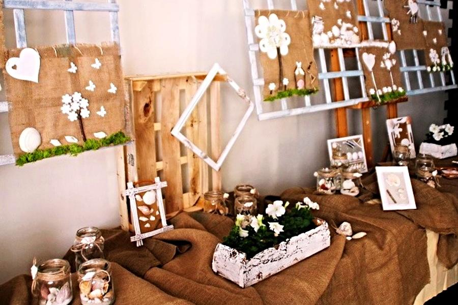 Na stole na jutowym obrusie stoją i leżą ozdoby wykonane na bazie słoików, sznurków, muszelek. Na ścianie wiszą obrazy wykonane z tych samych elementów