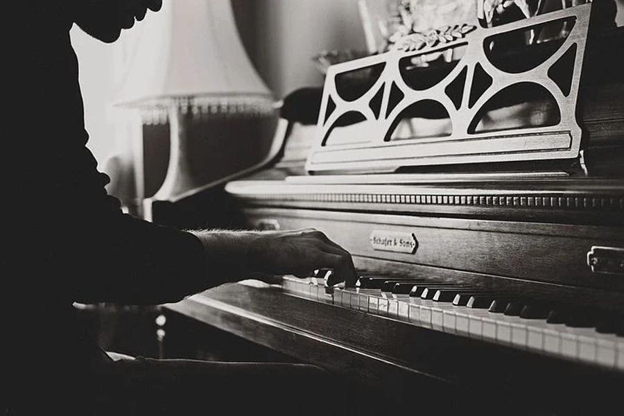 Na zdjęciu widać pianistę, grającego na zabytkowym fortepianie