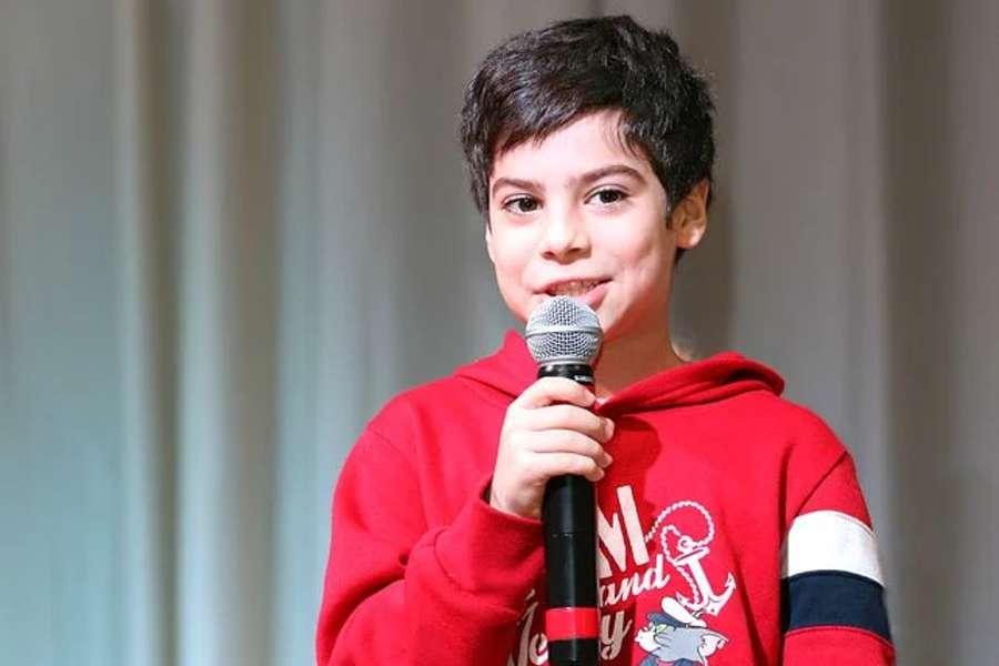 chłopiec w czerwonej bluzie, trzymający mikrofon