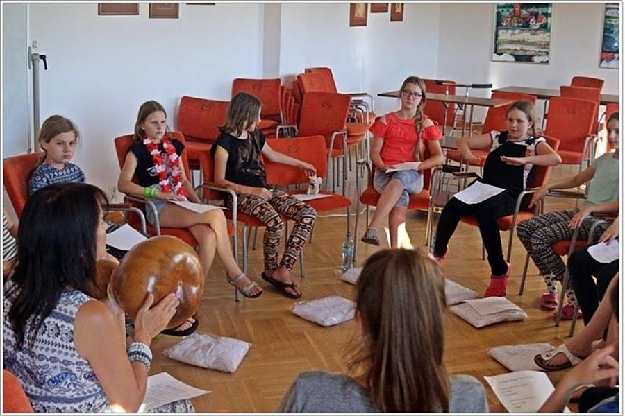 grupa dziewcząt siedzi na krzesłach w kole. W rękach trzymają kartki z tekstem. Kobieta siedząca tyłem trzyma tykwę