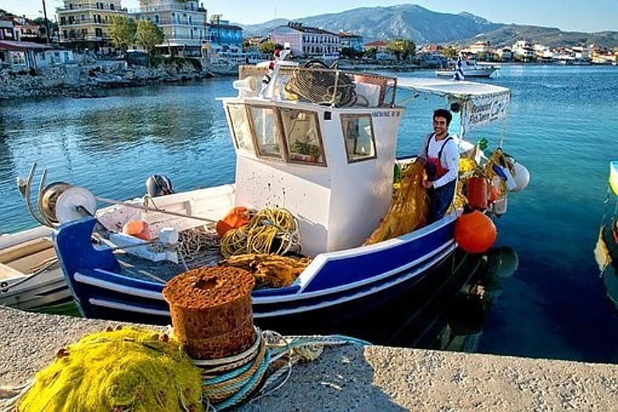 Przy nabrzeżu na wodzie mały kuter rybacki z rybakiem i sieciami na pokładzie