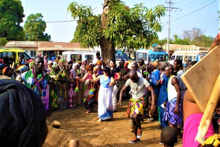 Grupa kobiet w kolorowych ubraniach z kijami w dłoni stoi w kole. W środku ludzie tańczą.