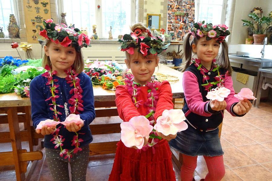 Trzy dziewczynki w wiankach i girlandach kwiatowych na szyi stoją obok siebie z wyciąg