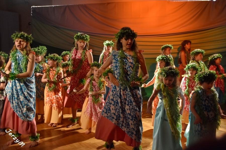Grupa dziewcząt ubranych w kolorowe parea w białe kwiaty, w zielonych wiankach na głowach, z kijami w dłoni bądź bez, tańczy na scenie i śpiewa.