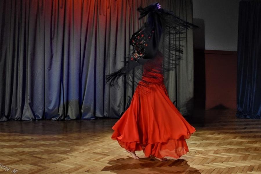 kobieta w czerwonej sukni i czarnek chuście tanczy flamenco