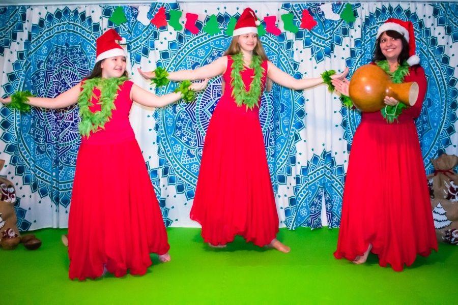 Dwie dziewczynki ubrane w czerwone suknie, w zielonych wiankach na głowach stoją z wyciągniętymi do boku rękami. Obok kobieta tak samo ubrana uderza w tykwę.