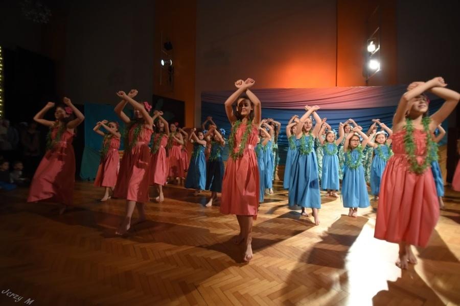 Grupa dziewcząt w różowych i turkusowych sukniach z kwiatami w tych samych kolorach tańczy na scenie trzymając ręce skrzyżowane przed sobą.