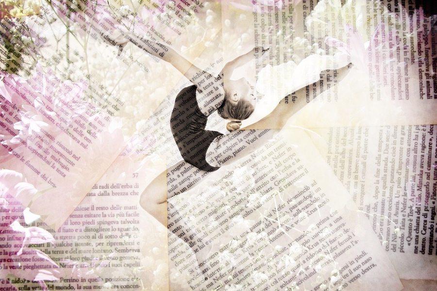 Zdjęcie przedstawia tancerkę w pozie arabesque na tle gazet