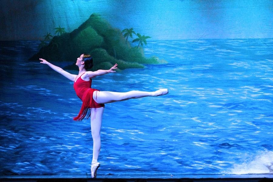 Zdjęcie przedstawia baletnicę w pozie arabesque.