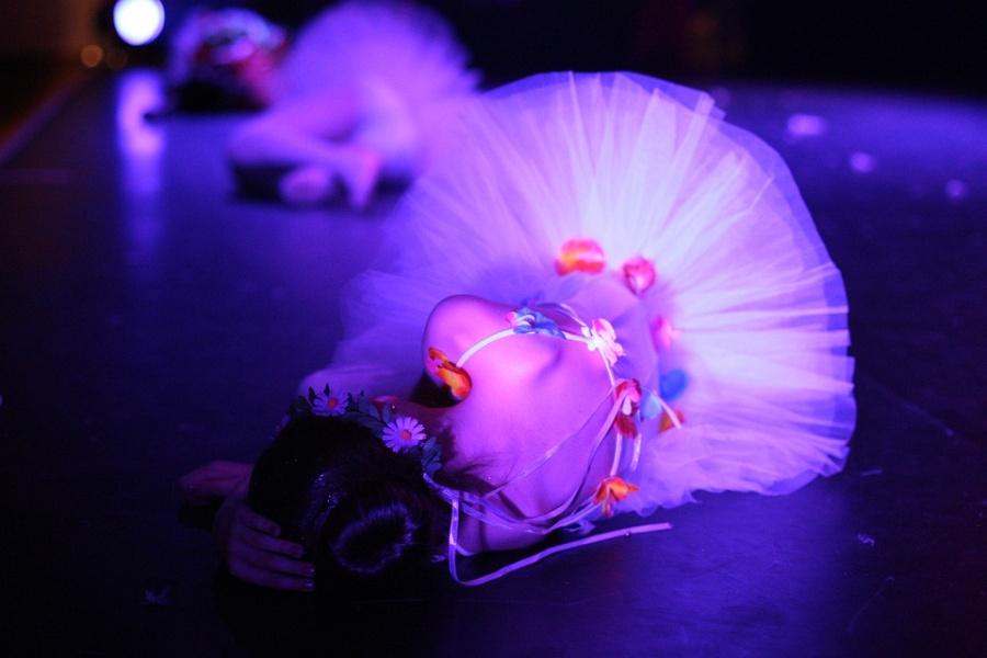 Zdjęcie przedstawia baletnicę leżącą na deskach sceny