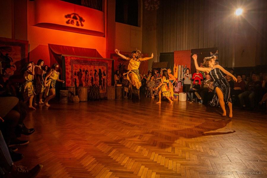 Dziewczyna w żółtym kostiumie wykonuje skok. W tle inne dziewczęta w tanecznych pozach.