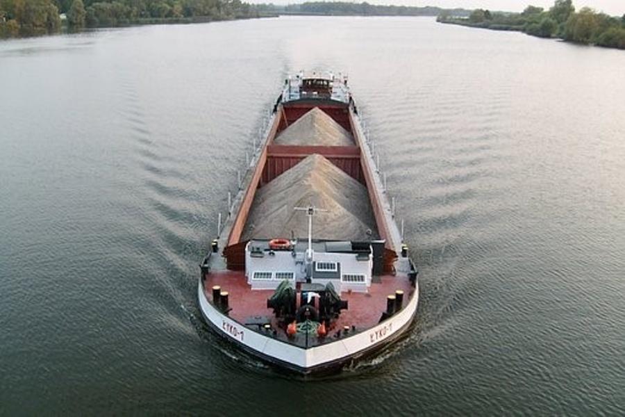 Barka załadowana piaskiem płynie po gładkich wodach szerokiej rzeki
