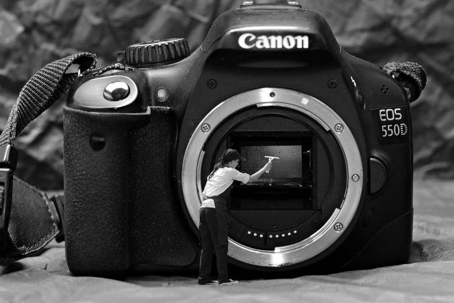 fotomontaż - aparat canon i postać dziewczyny która czyści obiektyw