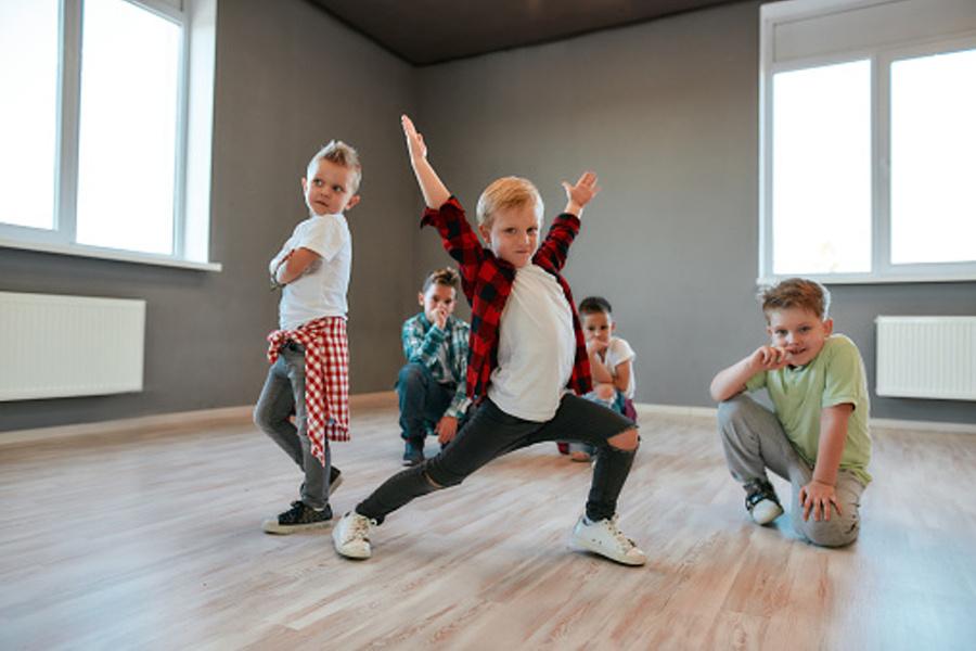grupa dzieci stojących w pozycjach tanecznych