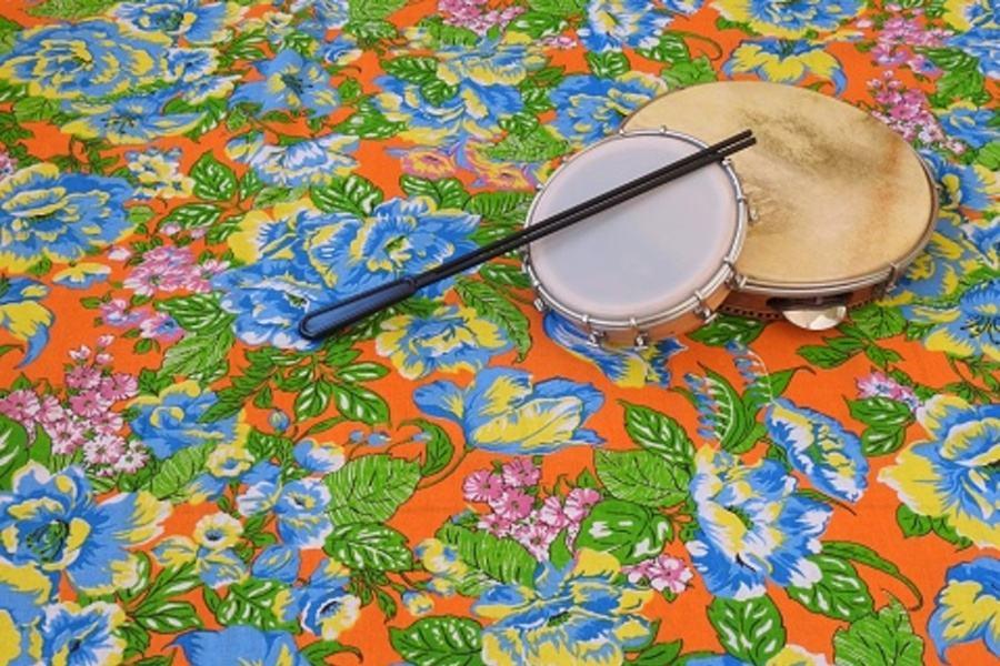 Zdjęcie przedstawia tamburyn i brazylijski tamborim oraz plastikową pałeczkę - wszystko leży na kolorowej wykładzinie