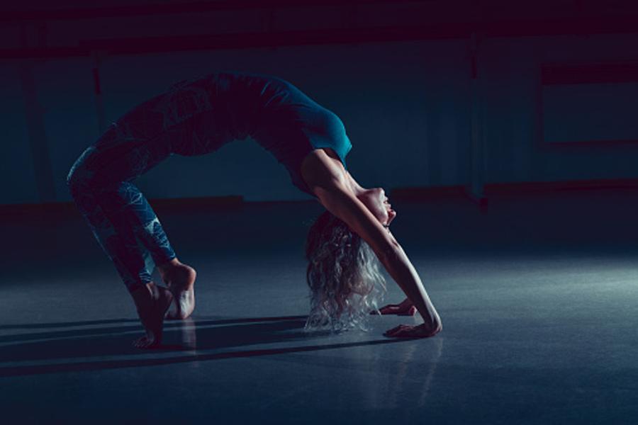 dziewczyna w niebieskim stroju robiąca mostek gimnastyczny