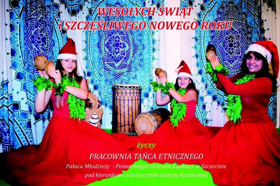 Dwie dziewczynki i kobieta ubrane w czerwone suknie z zielonymi wiankami na głowach siedzą trzymając w dłoniach kokosy. Na zdjęciu życzenia.