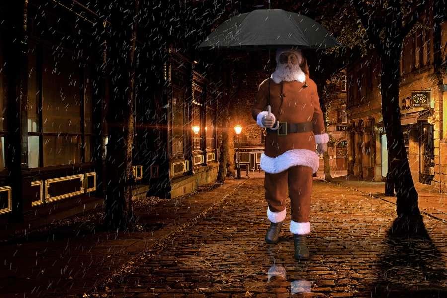 Zdjęcie przedstawia Mikołaja z parasolem w deszczowy wieczór