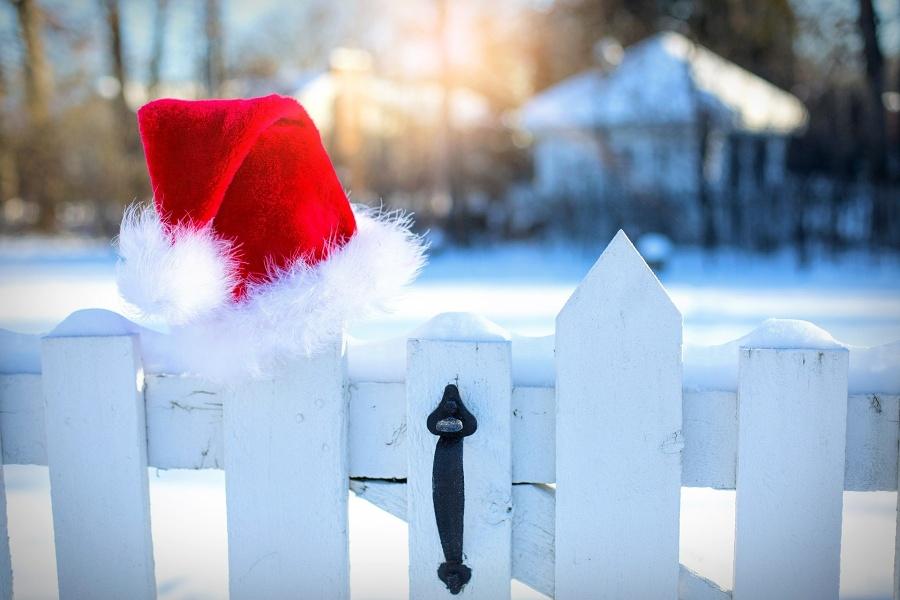 Zdjęcie przedstawia czapkę św. Mikołaja zaczepioną na białej furtce wejściowej, prowadzącej do domu w ośnieżonej scenerii.