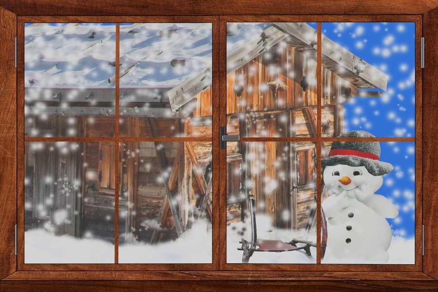 Zdjęcie przedstawia okno, chatę i wesołego bałwana