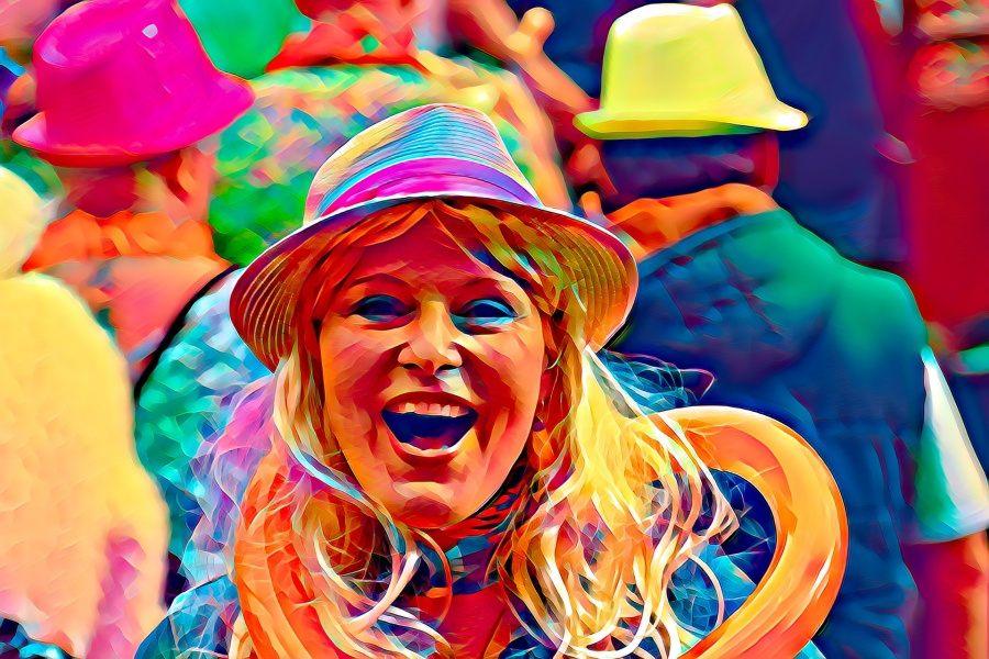 Zdjęcie przedstawia roześmianą twarz kobiety w kolorowym kapeluszu