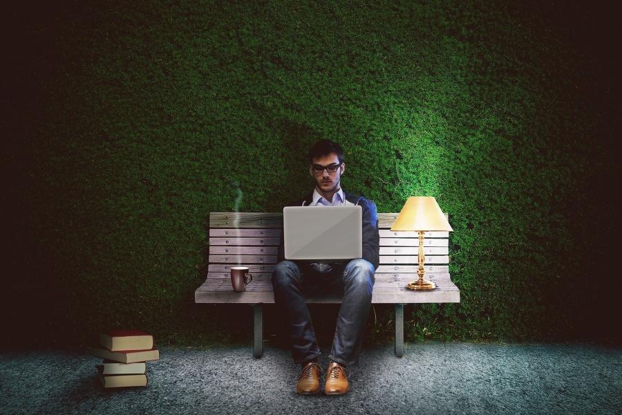 Zdjęcie przedstawia mężczyznę siedzącego na ławce, trzymającego na kolanach laptop.
