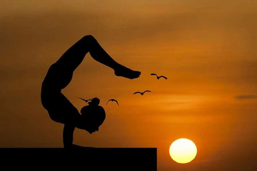 Zdjęcie przedstawia postać kobiecą ćwiczącą na tle zachodzącego słońca wśród latających ptaków.
