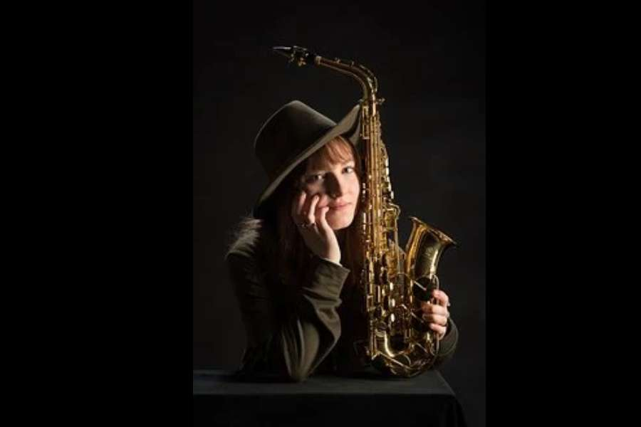 Na zdjęciu widać młodą dziewczynę w kapeluszu na ciemnym tle, trzymającą saksofon altowy