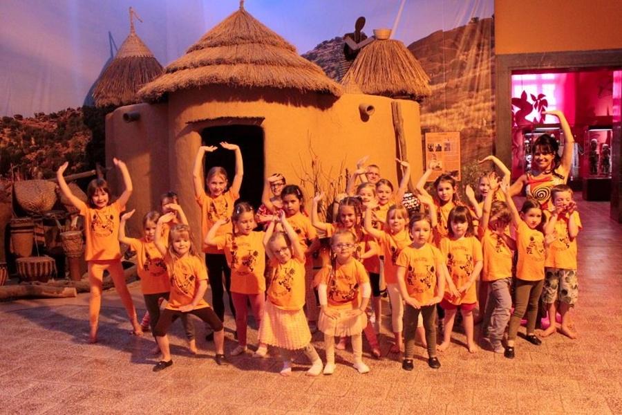 Grupa dzieci w pomarańczowych bluzkach oraz kobieta stoją w tanecznej pozie z rękami u góry przed chatami afrykańskimi.
