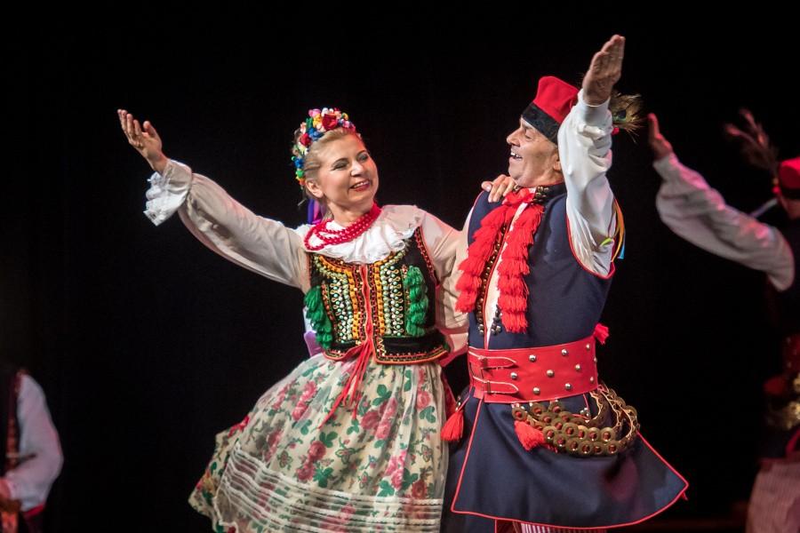 Para tańczące krakowiaka w tradycyjnych strojach krakowskich.