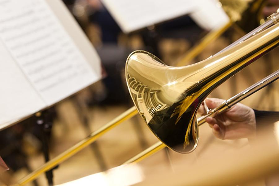 Na pierwszym planie widać puzon, na tle orkiestry symfonicznej.
