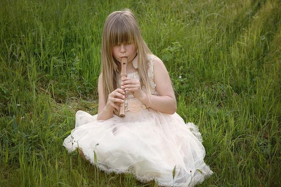 Na zdjęciu widać dziewczynkę w białej sukience,która siedzi na trawie i gra na flecie prostym.