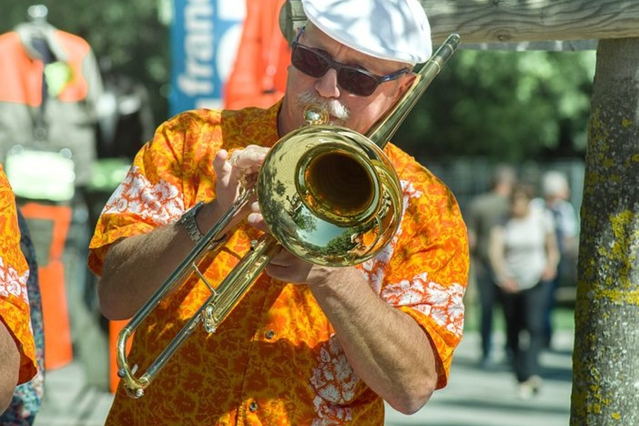 Na zdjęciu widać mężczyznę w kolorowej koszuli i białym kapeluszu, który gra na puzonie.