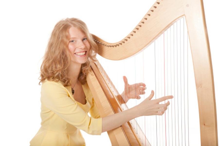 Na zdjęciu widać młodą uśmiechniętą kobietę,która gra na harfie