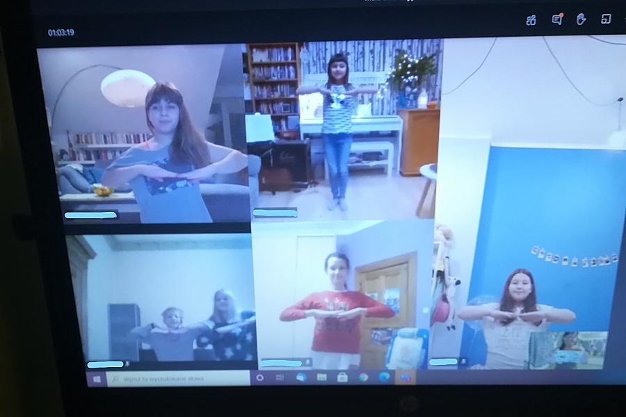Dziewczęta w tanecznych pozach widoczne w oddzielnych okienkach na ekranie komputera w trakcie zdalnej nauki tańca.