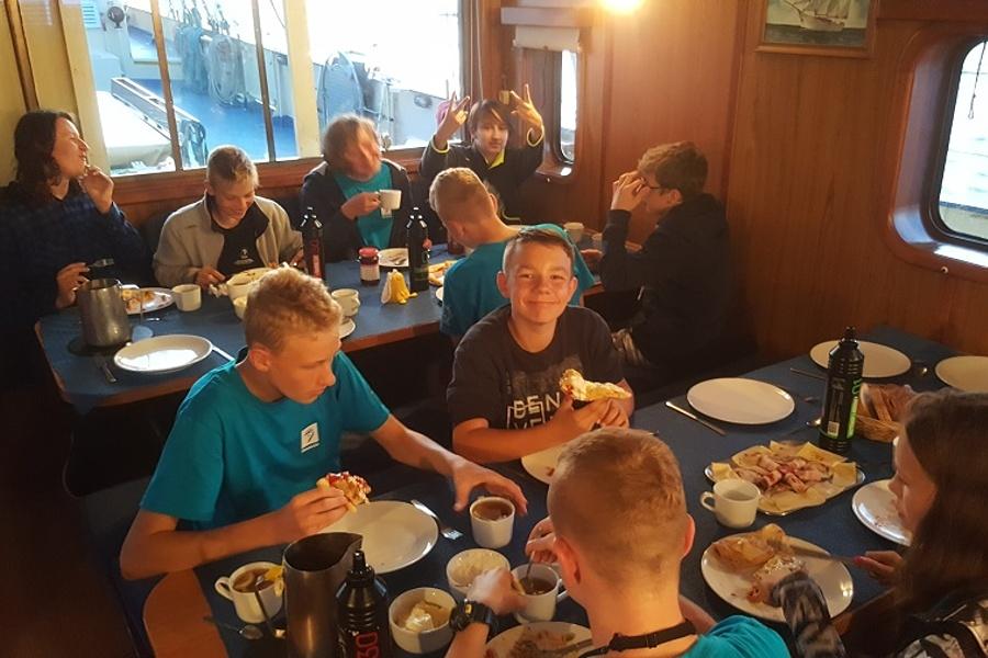 Mesa, grupa żeglarzy sześć osób spożywa posiłek przy stole zastawionym jedzeniem.