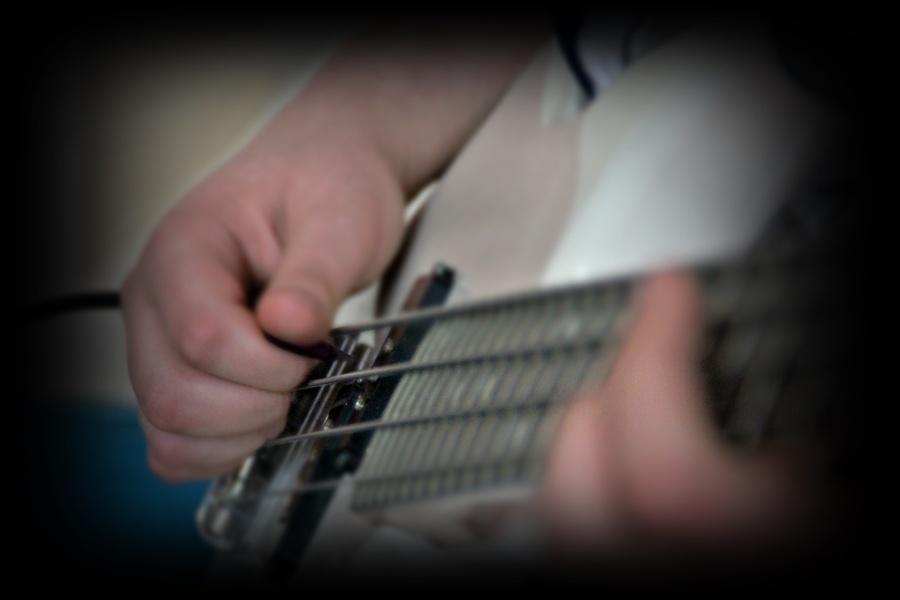 struny gitary basowej i dłonie na strunach