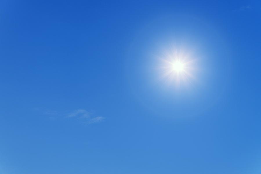 Białe słońce w lewym rogu na tle błekitnego nieba i przezroczysto-białych chmur