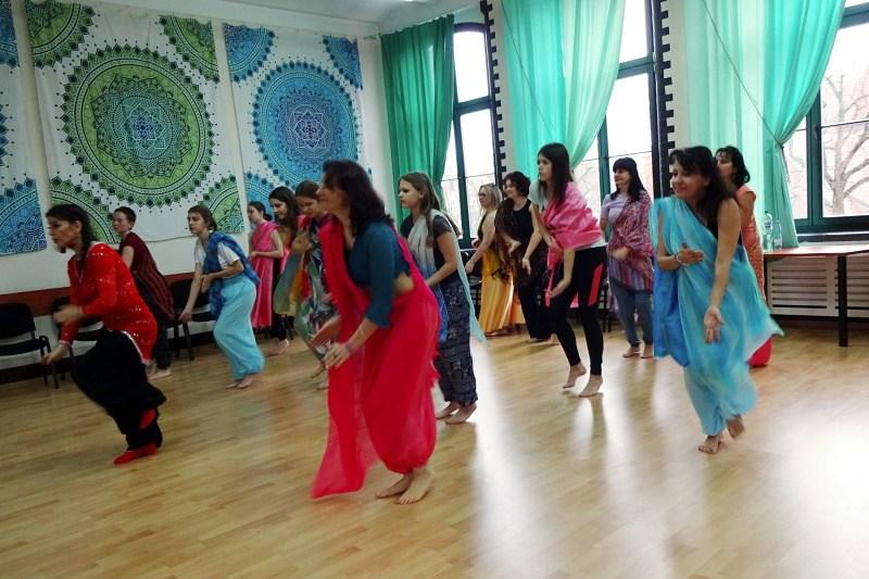 Grupa kobiet w różnym wieku, branych kolorowo z szarfą przewieszoną przez ramię stoi w pozie tanecznej