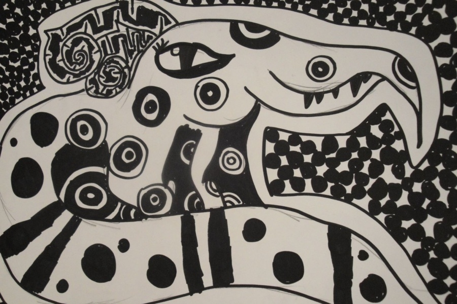 biało-czarna praca na której widać postać zwiniętego krokodyla lub smoka w duże wzory, który wyróżnia się z tła w drobne czarne kółka