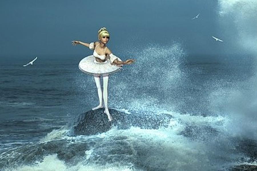 Zdjęcie przedstawia baletnicę stojącą na skale w samym środku oceanu i fruwające wokół niej mewy.