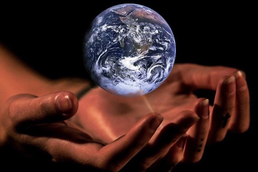 Zdjęcie przedstawia planetę Ziemię, unoszącą się nad ludzkimi dłońmi, które okalają ją w geście jej ochrony.
