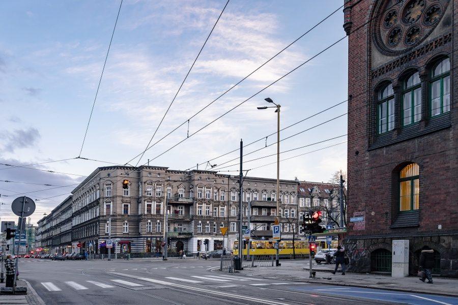 Zdjęcie skrzyżowania w mieście, po prawej stronie fragment budynku z czerwonej cegły z wysokimi oknami, na wprost szare kamienice na tle błekitnego nieba