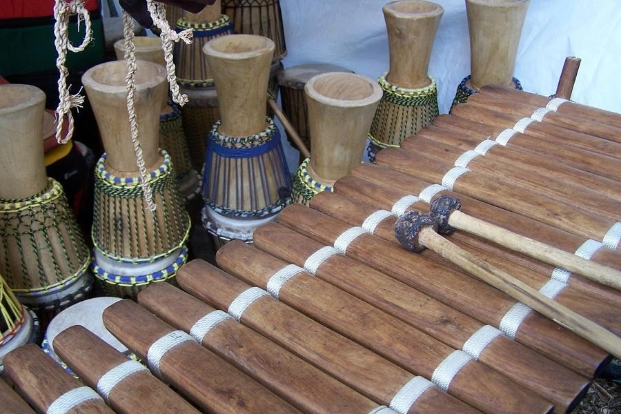 Zdjęcie przedstawia afrykański instrument zwany balafonem oraz odwrócone do góry nogami kilka afrykańskich bębnów pod nazwą djembe
