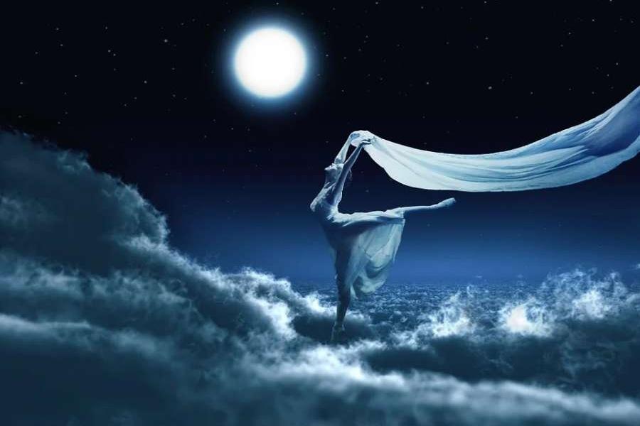 Zdjęcie przedstawia baletnicę z białą woalką stojącą w chmurach przy blasku pełni księżyca
