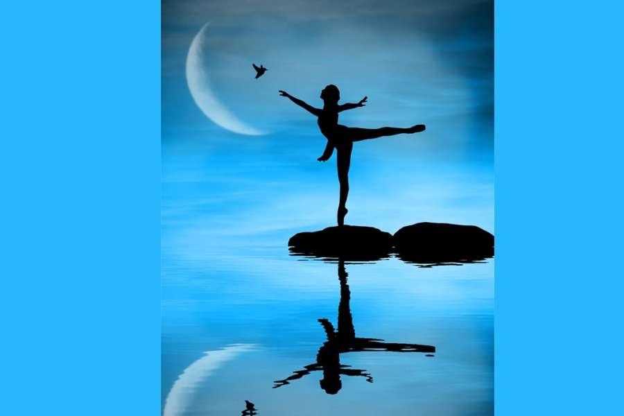 Zdjęcie przedstawia odbicie baletnicy w wodzie stojącej na kamieniu pięknej pozie arabesque