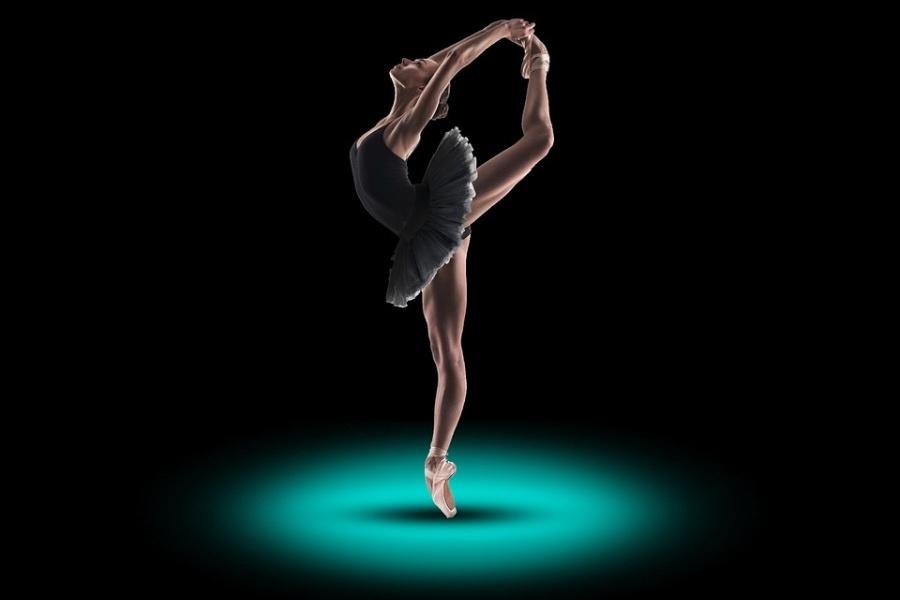 Zdjęcie przedstawia baletnicę stojącą w pięknej pozie na pointach