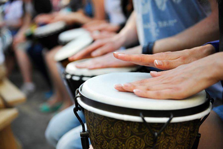 Na zdjęciu widocznych jest wiele dłoni grających na kilku djembe