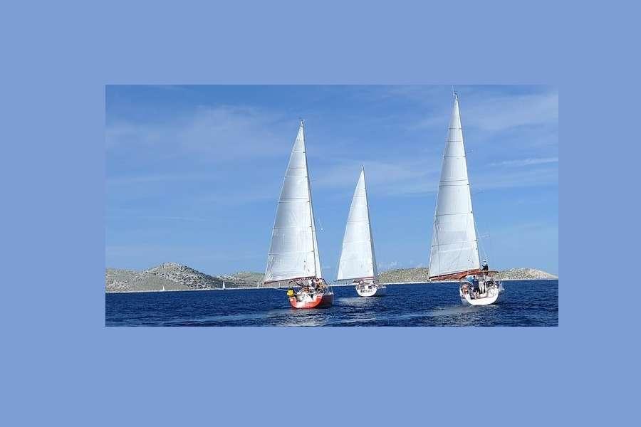 Trzy jachty płyną pełnym kursem po morzu na horyzoncie widoczne pagórkowate wyspy