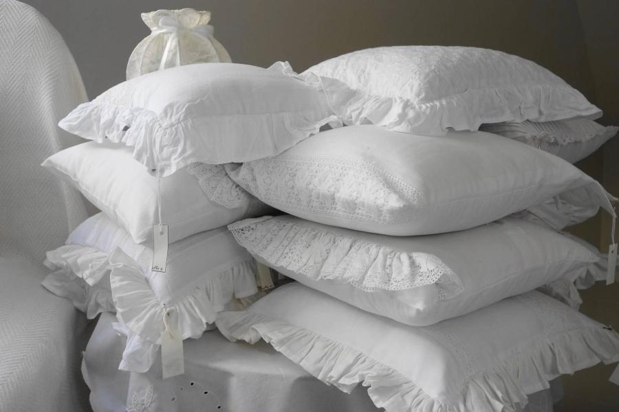 Zdjęcie przedstawia dwie sterty białych, koronkowych poduszek